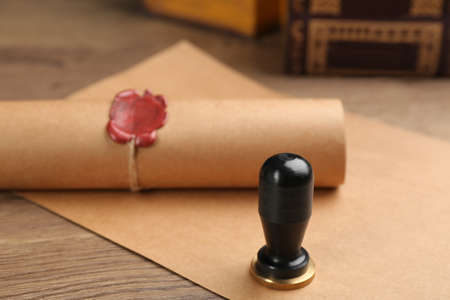 Notarys public pen and document with wax stamp on wooden table, closeup
