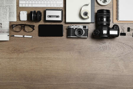 Flat lay composition with equipment for journalist on wooden table. Space for text