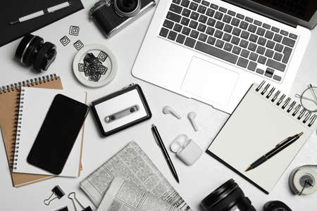 Flat lay composition with equipment for journalist on white table
