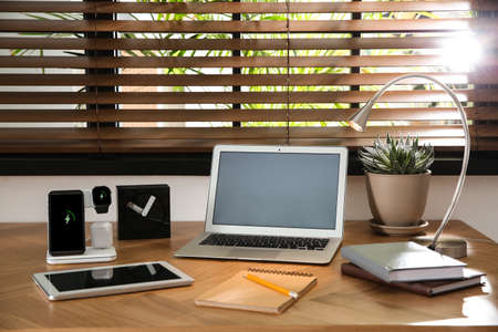 Mobile phone, earphones and smartwatch charging with wireless pad on wooden desk. Modern workplace device Foto de archivo