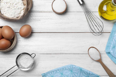 Flat lay composition with ingredients on white wooden table, space for text. Cooking thin pancakes
