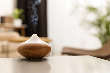 Aroma oil diffuser on light table at home, space for text. Air freshener Banque d'images