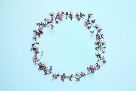 Frame made of beautiful flowers with space for text on light blue background, top view. Floral card design Stockfoto