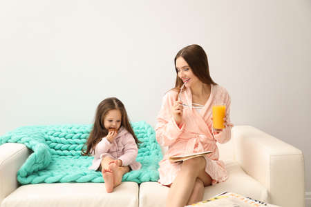 Mother and daughter in bathrobes sitting on sofa