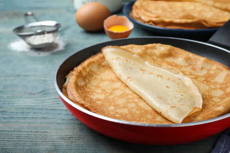 Delicious thin pancakes on blue wooden table, closeup