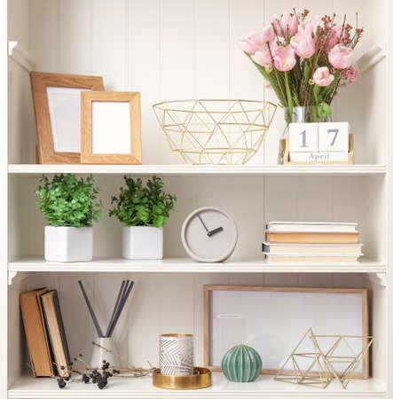 Estantería blanca con plantas y diferentes elementos decorativos.