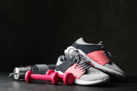 Gym equipment and accessories on stone floor against dark background Reklamní fotografie