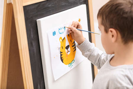 Little child painting on easel in room