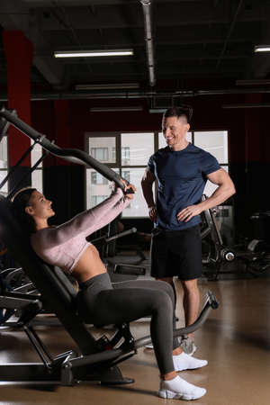 Trainer with young woman working out on chest press machine in gym