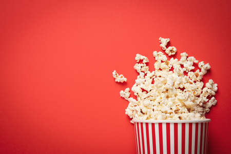 Overturned paper cup with delicious popcorn on red background, top view. Space for text