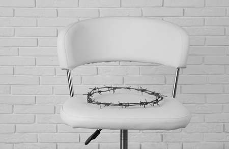 Chair with barbed wire near white brick wall. Hemorrhoids concept