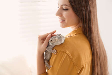 Young woman with bearded lizard at home. Exotic pet