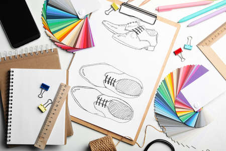 Flat lay composition with drawing of shoes on white table. Designer's workplace