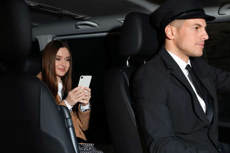 Professional driver and businesswoman in luxury car. Chauffeur service