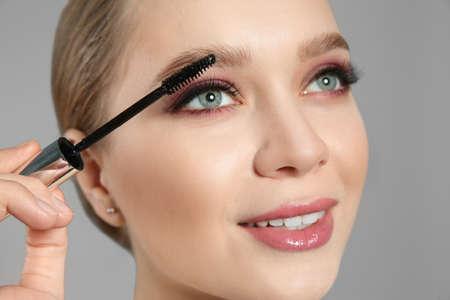 Beautiful woman applying mascara on light grey background. Stylish makeup