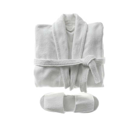 Clean folded bathrobe and slippers isolated on white, top view