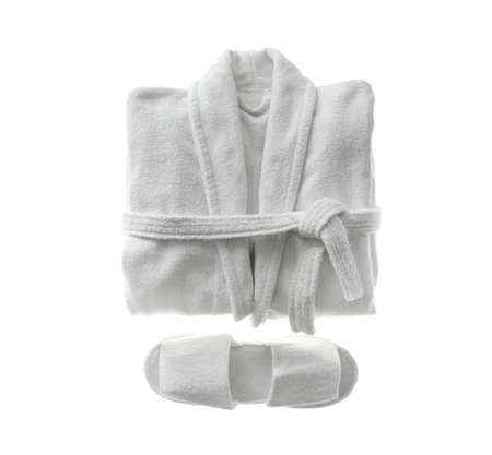 Sauber gefalteter Bademantel und Hausschuhe isoliert auf weiß, Ansicht von oben