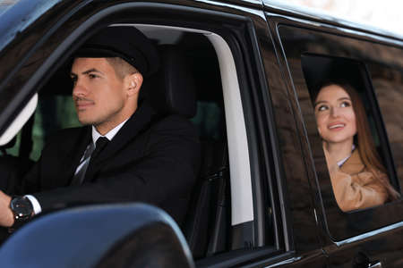 Professional driver and businesswoman in luxury car. Chauffeur service Foto de archivo