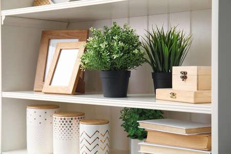 White shelving unit with plants and different decorative stuff Foto de archivo