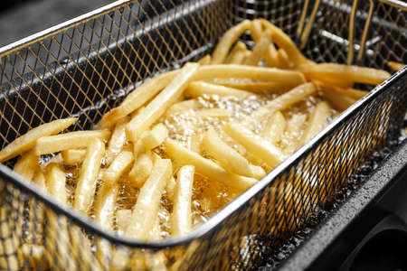 Cooking delicious french fries in hot oil, closeup