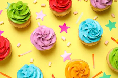 Bunte Geburtstagskuchen auf gelbem Hintergrund, flach Standard-Bild