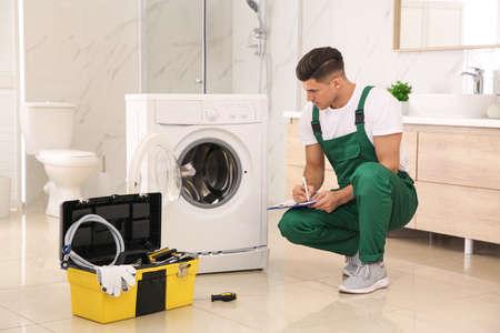 Professioneller Klempner repariert Waschmaschine im Badezimmer