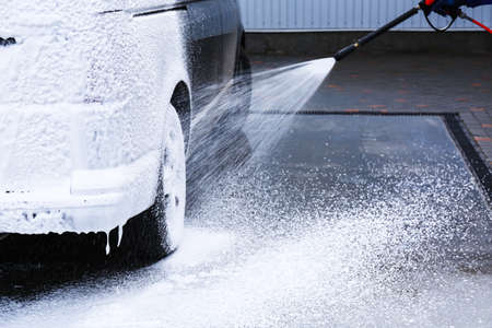 Covering automobile with foam at car wash