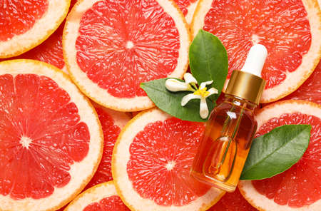 Bottle of citrus essential oil and flower on pile of grapefruit slices, flat lay. Space for text