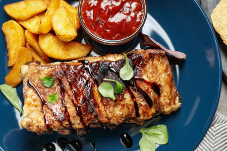 Delicious grilled ribs with potatoes and sauce on table, top view