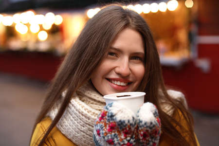Happy woman with mulled wine at winter fair Foto de archivo