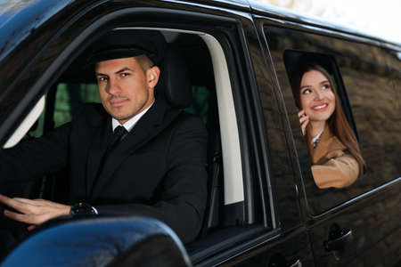 Professional driver and businesswoman in luxury car. Chauffeur service Stok Fotoğraf