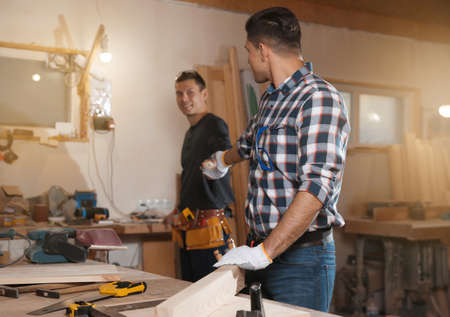 Carpenter giving tool to colleague in workshop
