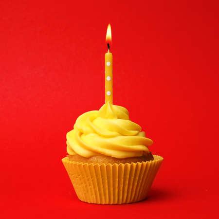 Cupcake de cumpleaños delicioso con crema amarilla y velas encendidas sobre fondo rojo.