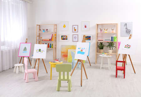 Easels with paintings and chairs for children in room