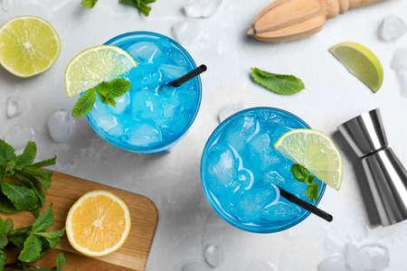 Flache Komposition mit Blue Lagoon Cocktail auf hellgrauem Marmortisch