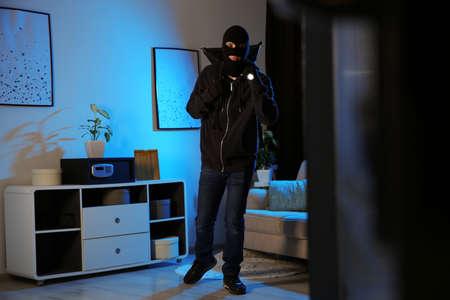 Thief with flashlight near steel safe indoors at night