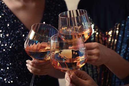 Las mujeres tintinean vasos con vino blanco, primer plano