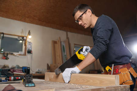 Professional carpenter sawing wooden plank at workbench