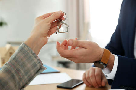 Real estate agent giving key with trinket to client in office, closeup
