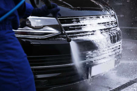 Worker cleaning automobile with high pressure water jet at car wash, closeup 版權商用圖片