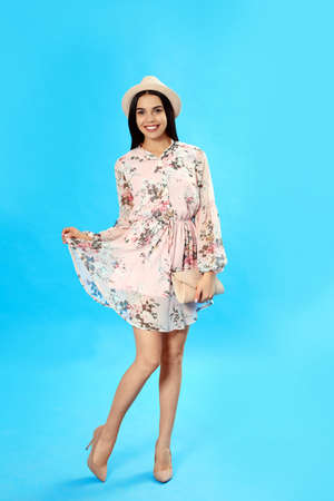 Young woman wearing floral print dress with clutch on light blue background
