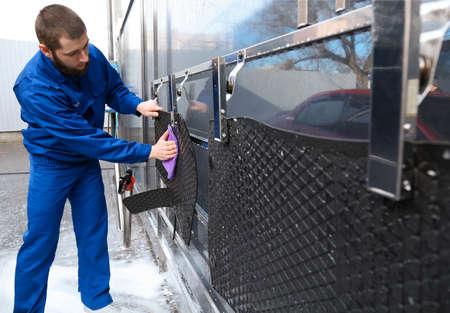 Worker wiping automobile floor mat at car wash Zdjęcie Seryjne
