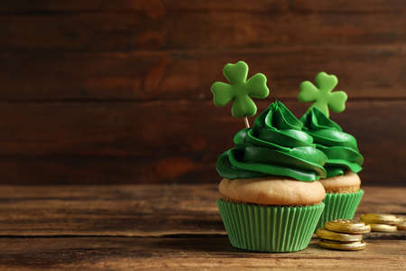 Delicious decorated cupcakes on wooden table, space for text. St. Patrick's Day celebration