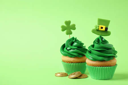 Delicious decorated cupcakes and coins on light green background, space for text. St. Patrick's Day celebration