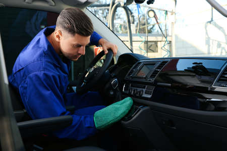 Car wash worker cleaning modern automobile interior