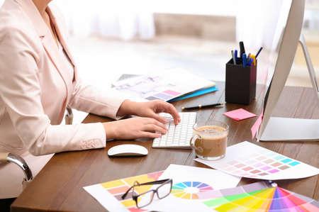 Female designer working at desk in office, closeup