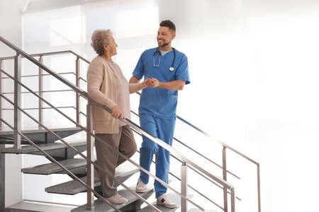 Doctor helping senior patient in modern hospital