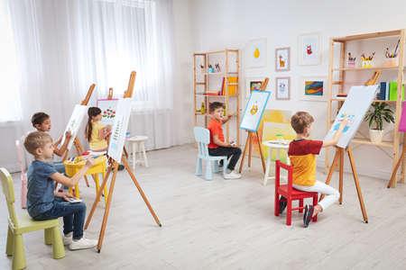 Petits enfants mignons peignant pendant la leçon dans la chambre