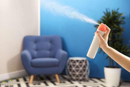 Woman spraying air freshener at home, closeup Standard-Bild
