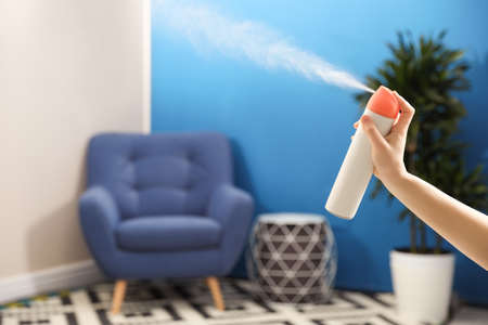 Woman spraying air freshener at home, closeup